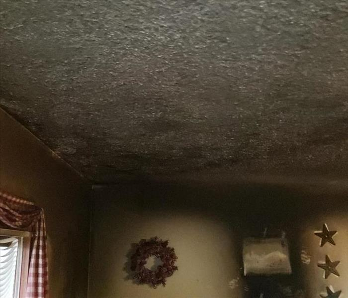 Smoke and soot damage to the walls and ceiling of a residential property