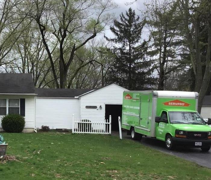 A Green SERVPRO Truck parked in front of a white ranch house.